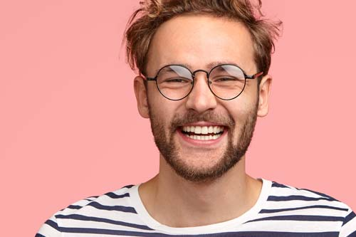 specialist services man with glasses smiling pink backdrop
