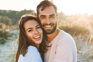 couple smiling at the beach with teeth brightened from cosmetic dentistry meyerland plaza tx