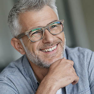senior man with glasses smiling to show dental implants