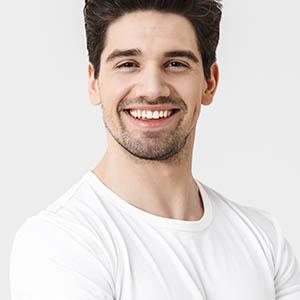 man in white smiling to show off teeth whitening from lovett dental meyerland plaza