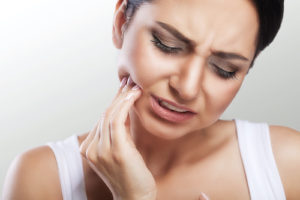 Woman struggles with the pain caused by her impacted teeth